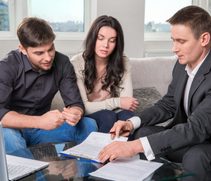 Couple,Consults,With,Agent,,Signing,Paperwork